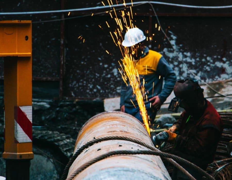 Männer auf einem Schrottplatz bearbeiten ein großes Roher aus Metall