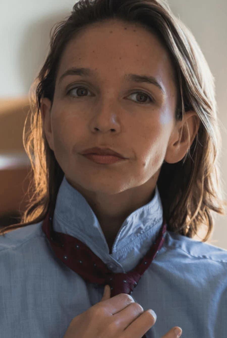Eine Schrotthändlerin bindet sich eine Krawatte